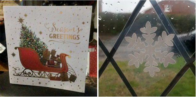 A Christmas card and a snowflake decoration on the window
