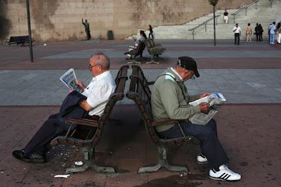 Pensionistas leyendo periódicos gratuitos en bancos públicos de Madrid.Susana VeraReuters