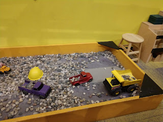 wooden sandbox filled with landscaping rocks, toy trucks, and a yellow plastic hard hat at LaunchPad Children's Museum in Sioux City Iowa