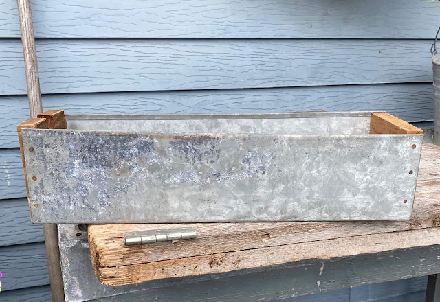 Photo of a galvanized industrial drawer/bin with wooden ends.