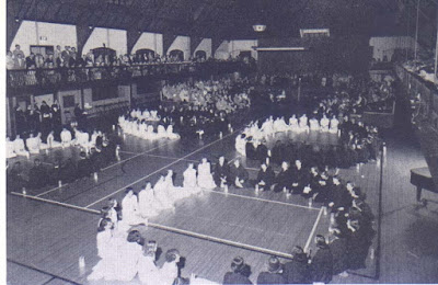 girls seated in the gym in circles, half of each circle wearing white and the other half wearing black