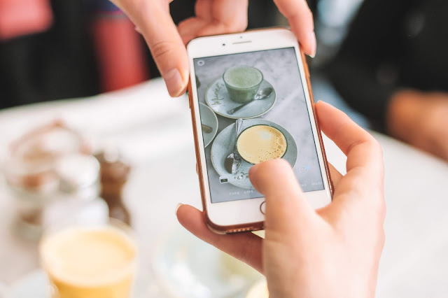 person taking photo of coffee with iphone