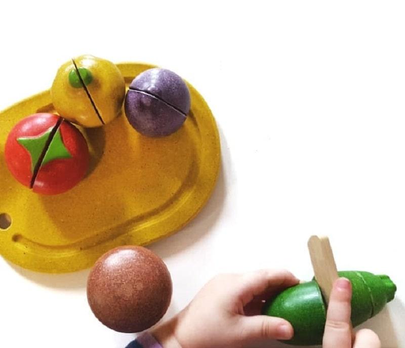 toddler cutting wooden cucumber