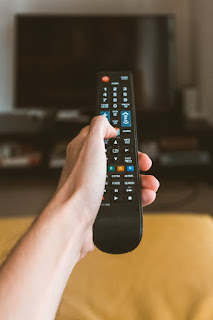A person changing the TV station using a black remote control
