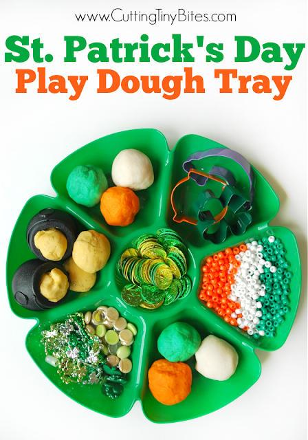 St. Patrick's day playdough tray with yellow playdough in black cauldrons, orange, and white, and green, playdough, orange, white, and green beads, green and gold coins, St. Patrick's day faux gems, and necklaces, and cookie cutters.