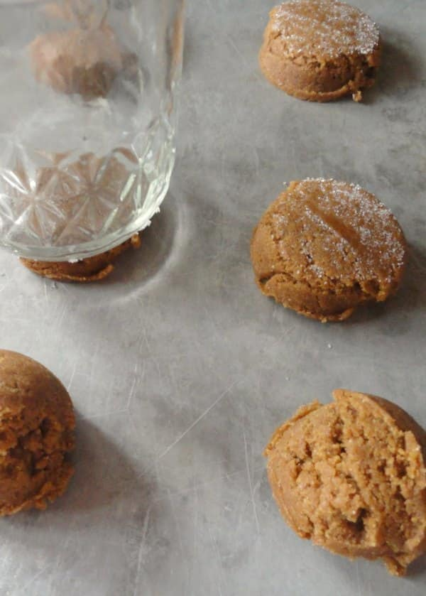 Molasses Cookie Dough Balls being pressed flat with a glass dipped in sugar.