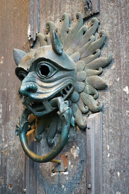 Photograph of the Durham Cathedral sanctuary knocker: a metal face, demonic in appearance, with a ring in its mouth, on a heavy wooden door.