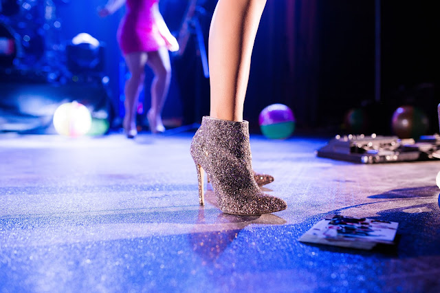 womans leg in very sparkling boots on a dance floor