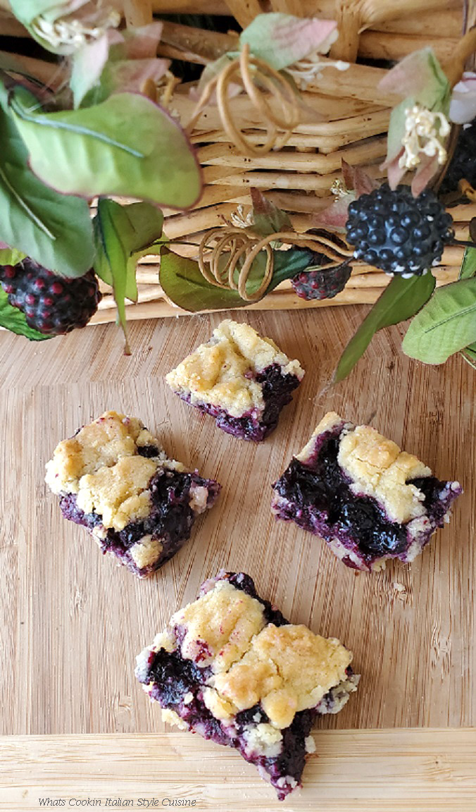 this is blueberry bars on a wooden platform with berry on a wicker basket in the background