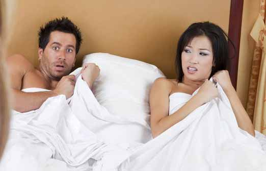 A man and a woman caught in bed naked cheating.
