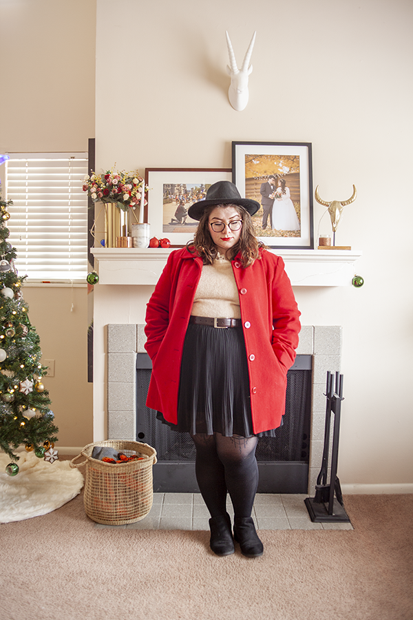 An outfit consisting of a black wide brim hat, a red coat, a cream colored sweater tucked into a black pleated knee length skirt and black ankle boots.
