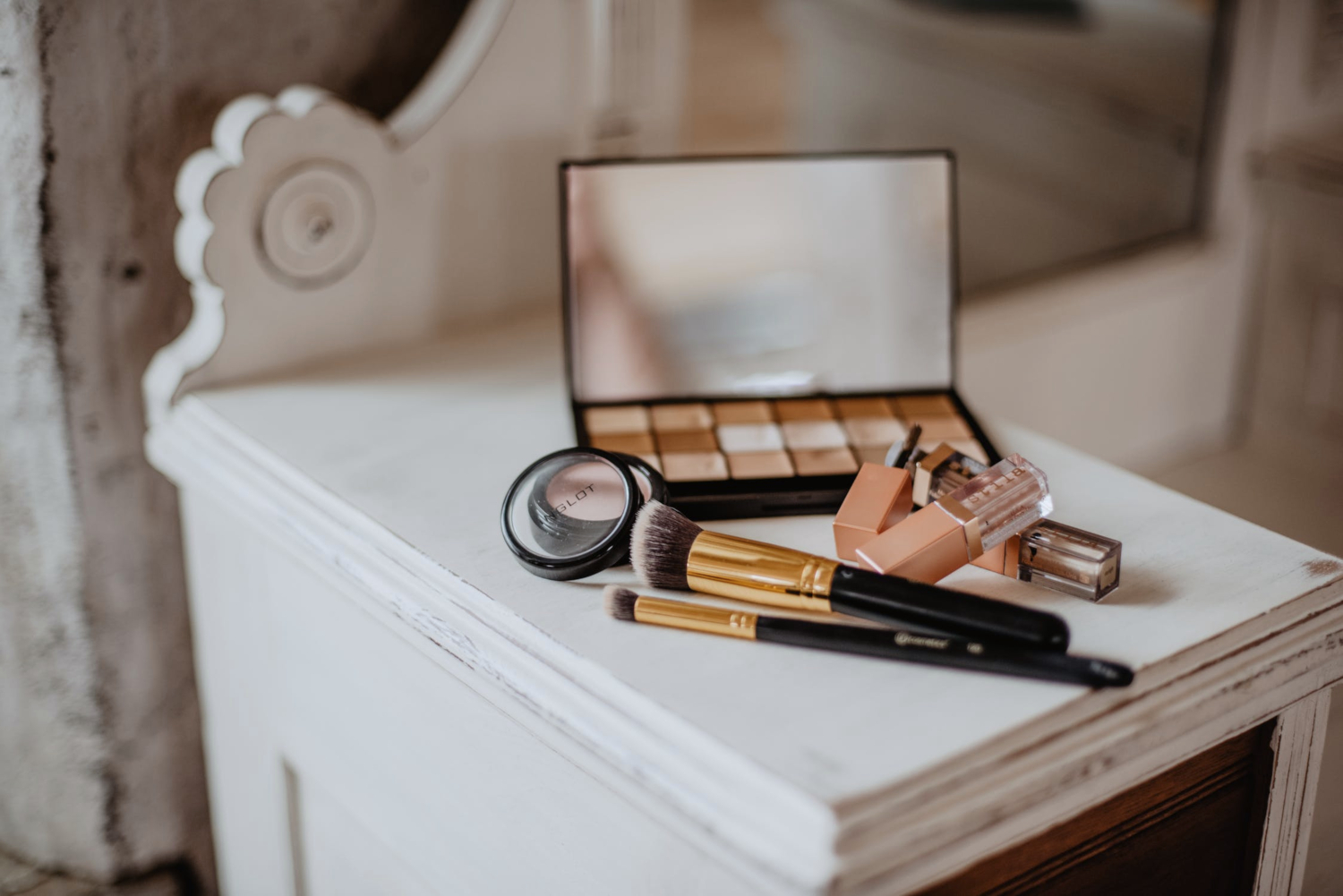 a close up picture of a makeup stash that is laying on a wooden vanity