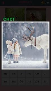 зимой на снегу олень, перед которым стоят две девочки