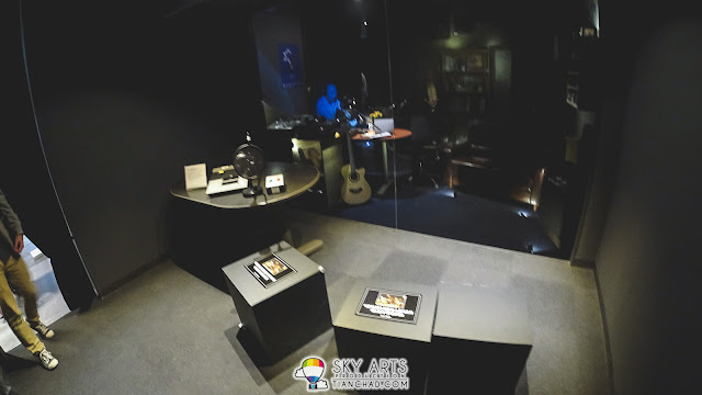 An old-style radio announcer room. The blue human figure is actually a broadcasted visual image.