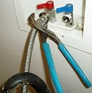 Use Channel Locks pliers to tighten the hot water hose to the washer
