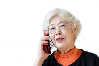 補聴器を使って電話をするも、聞き取れず不快に思っている女性。