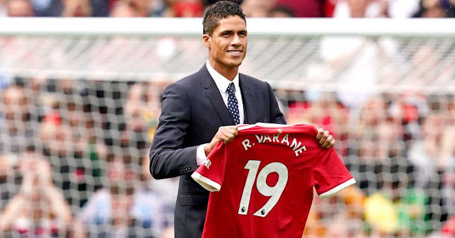 Raphael Varane pictured holding a Manchester United shirt