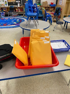student yellow folder packets in a red bin
