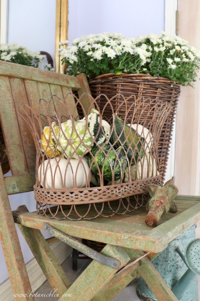Keep a tight color palette for a French Country rustic fall entry with white mums and small green gourds