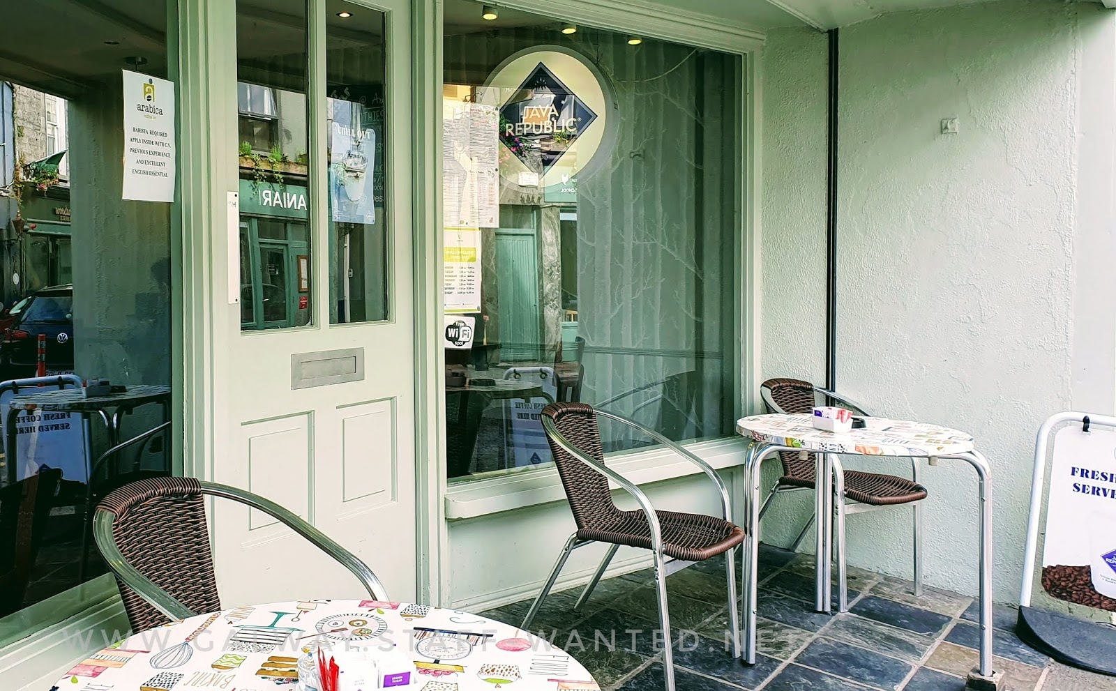 cafe outdoor seating area beside the front door - metal-legged round tables, metal-legged chairs with imitation cane wicker-work style seats
