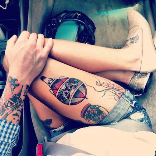 chica sentada en coche con tatuaje en la pierna de globo