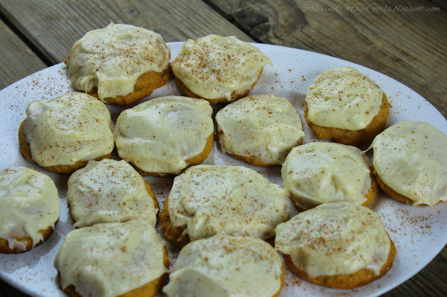 Iced Pumpkin Spice Cookies on white platter on wooden table