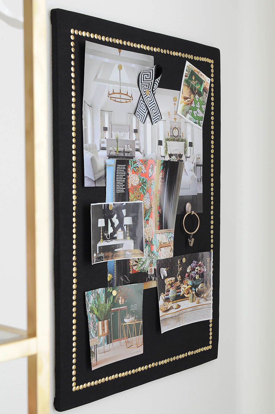 A beautiful linen and gold nailhead pinboard in a bright white and gold home office.