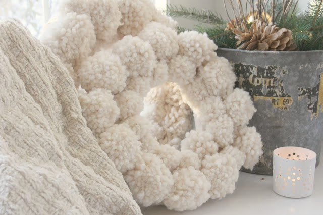 White holiday wooly pom pom wreath and galvanized bucket with fresh greenery