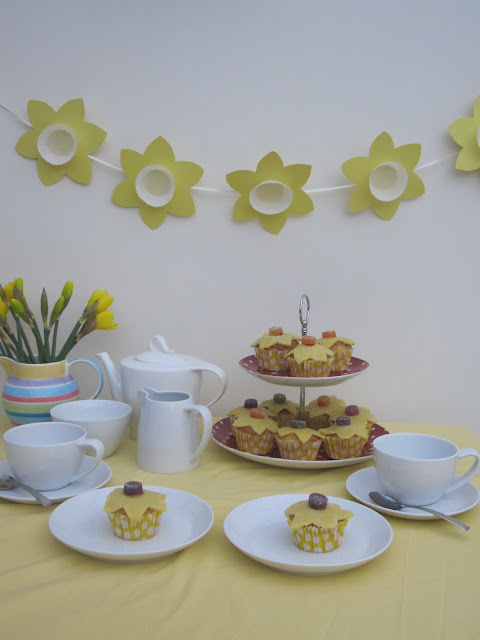A table set for afternoon tea with cups and saucers, cupcakes on a stand, teapot and a jug filled with fresh daffodils