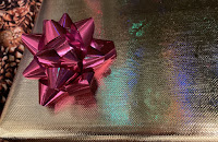 Christmas present wrapped in textured gold wrapping paper.