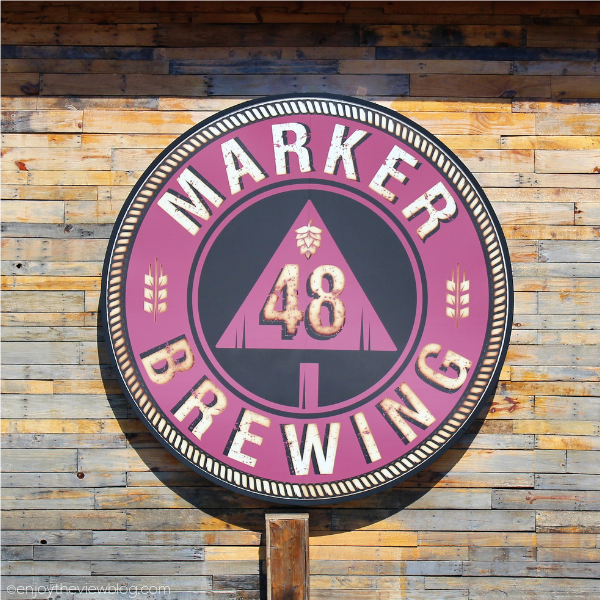 "round sign on a building that says ""Marker 48 Brewing"""