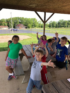 First grade students sitting on a bench with hands in the air