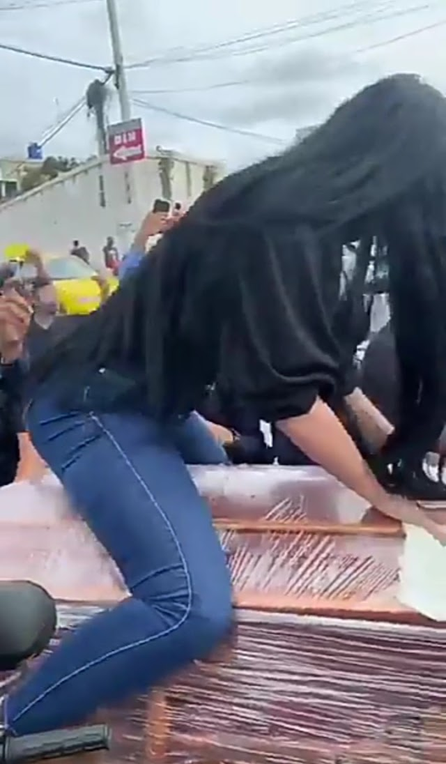 Moment Lady Twerks on Top of half-open coffin at a funeral.