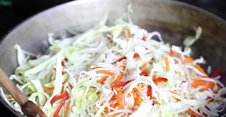 Step 1. Cook the vegetables  With vegetable oil heat the wok. Add carrots, red pepper, bamboo shoots, bean flower, and cabbage. Cook it all together until it's softened slightly.
