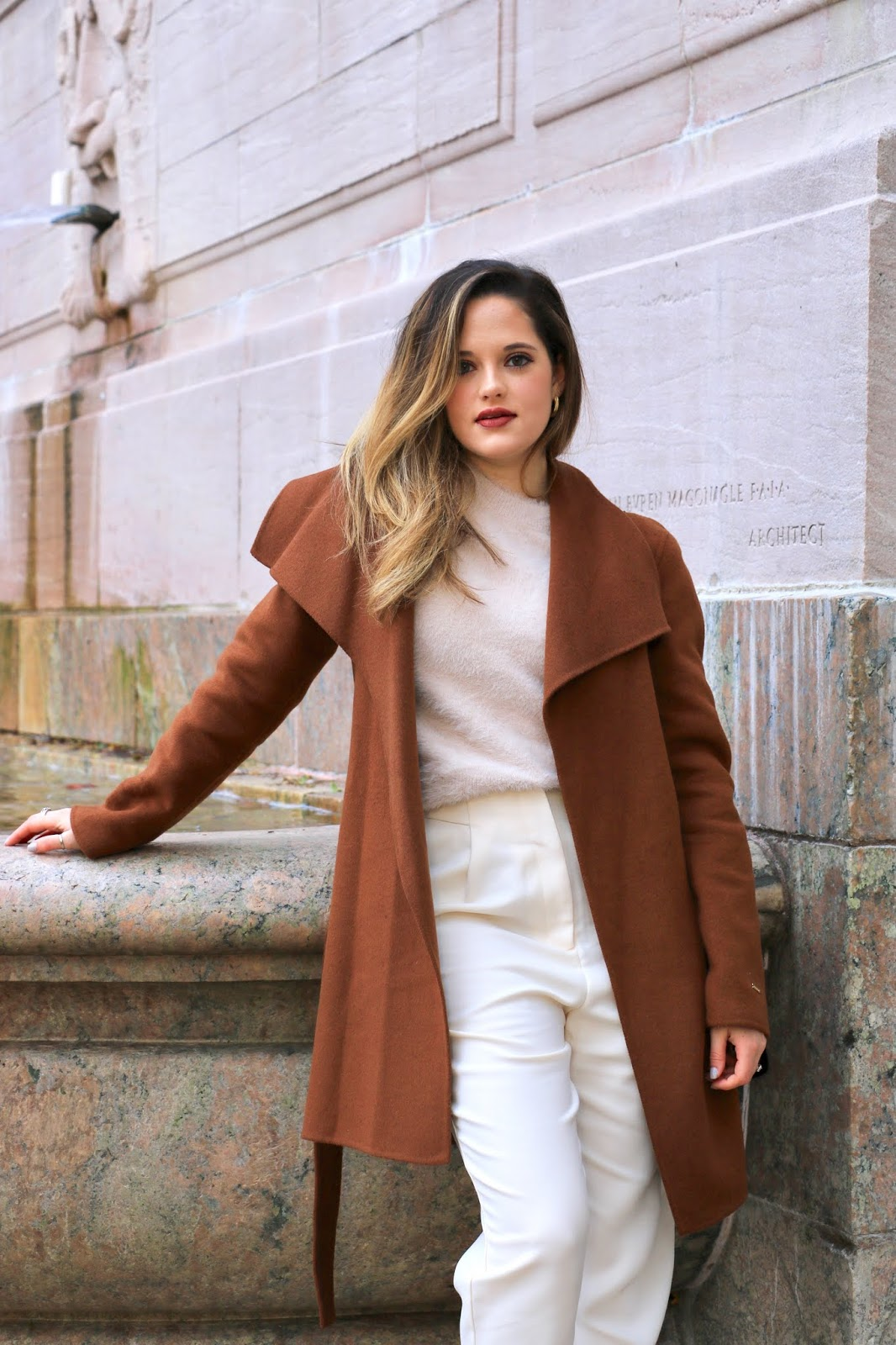 Nyc fashion influencer Kathleen Harper wearing a cream outfit with a camel wrap coat.