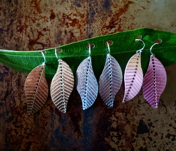 Metallic leather earrings in gold, silver, and rose gold colors in the shape of leaves.