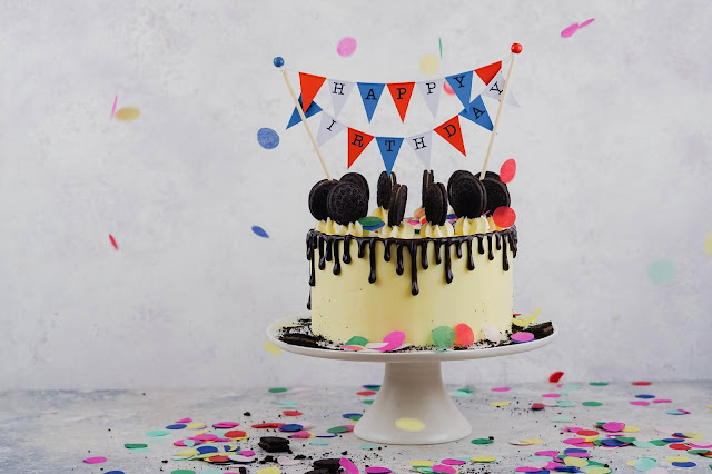The image shows a birthday cake with a happy birthday bunting and confetti on the table