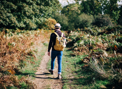 man wearing backpack walking along a path
