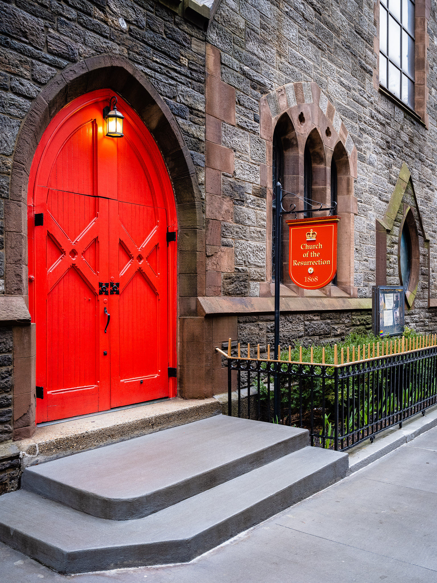 a photo of a church with a red door and red sign in new york city