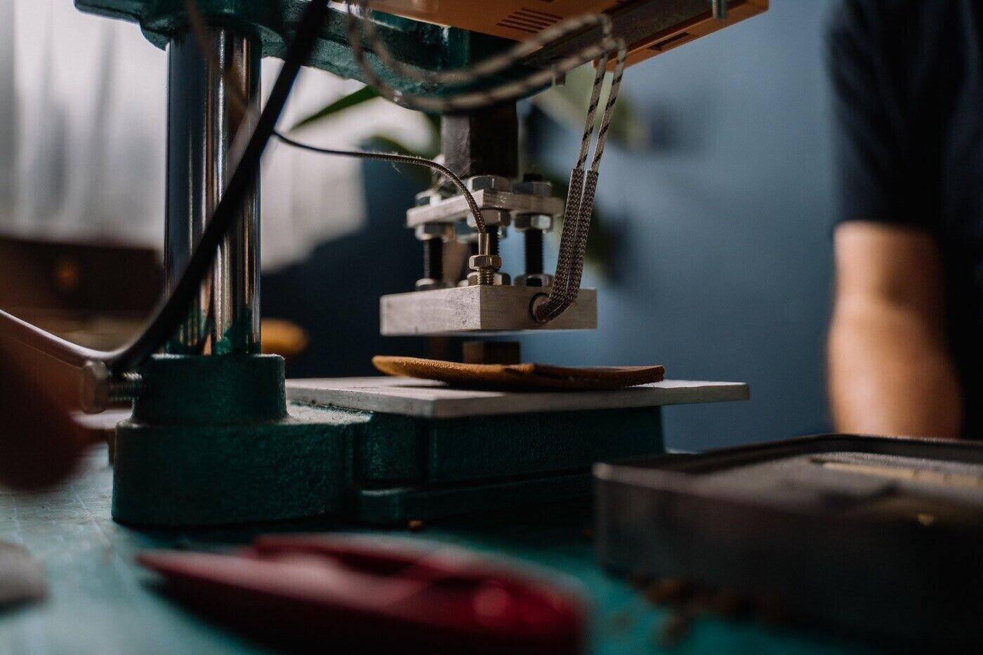 close up of industrial sewing machine with man's arm in background - how to make ethical fashion part of your wardrobe
