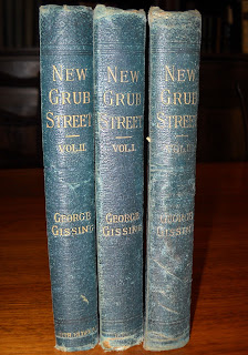 "A photograph of three volumes of ""New Grub Street."""