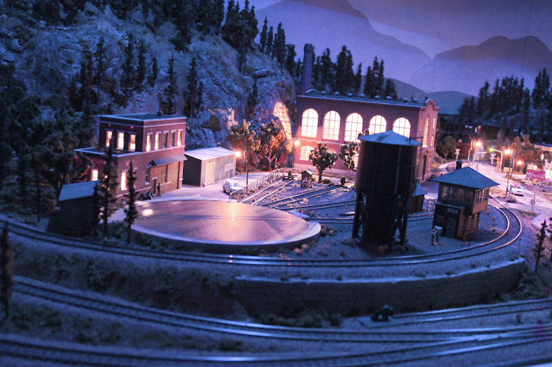 HO scale model railroad layout railyard scene at night with accessory lighting effects