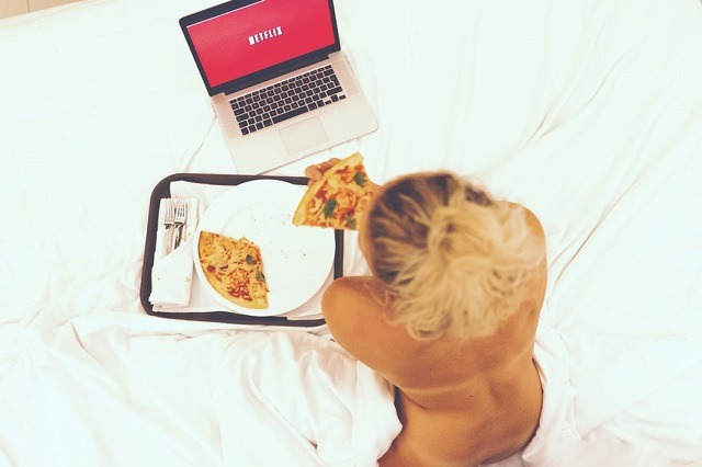 woman watching netflix eating pizza on bed naked