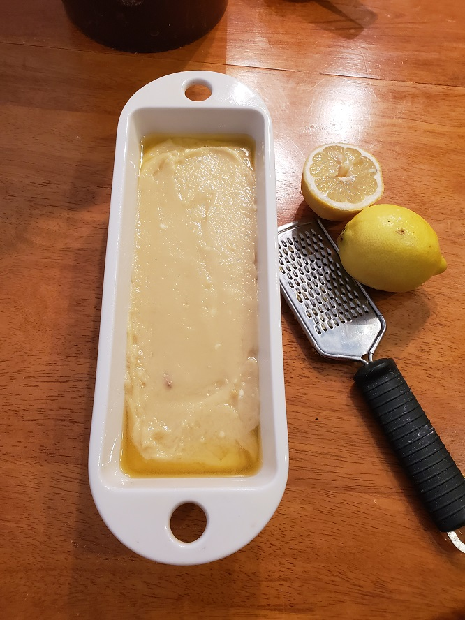 This is the batter in a loaf pan for Starbucks lemon loaf. It's a copycat recipe. There is also lemon cut in half with the grater in this photo?