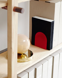 bookshelf with red bookends and glass globe light