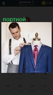 портной мужчина шьет пиджак, снимает мерки