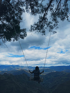 Girl on swing with a view of Loja, Ecuador