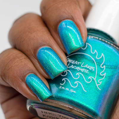 A sheer turquoise nail polish base filled with an emerald to blue to purple to magenta shifting aurora shimmer on dark skin
