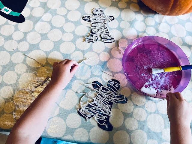 Making halloween mummies by gluing short pieces of string onto a gingerbread man shaped piece of black card