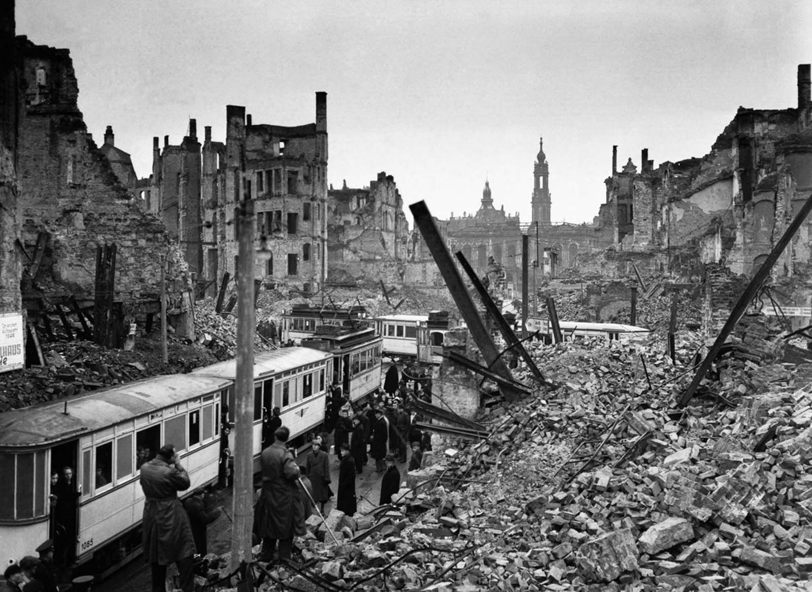 Residents ride trams through the rubble of the city. 1946.